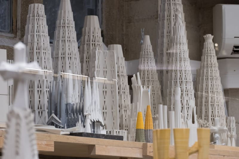 A photo of many small white models of roof spires of la Sagrada Família.