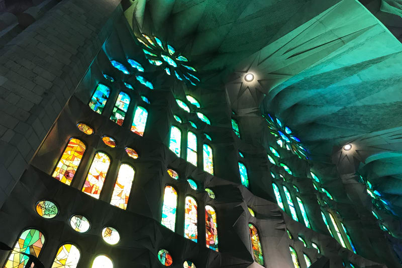 Looking up at some stained glass windows in la Sagrada Família. The near ceiling is faceted and coloured green and blue from the window light.