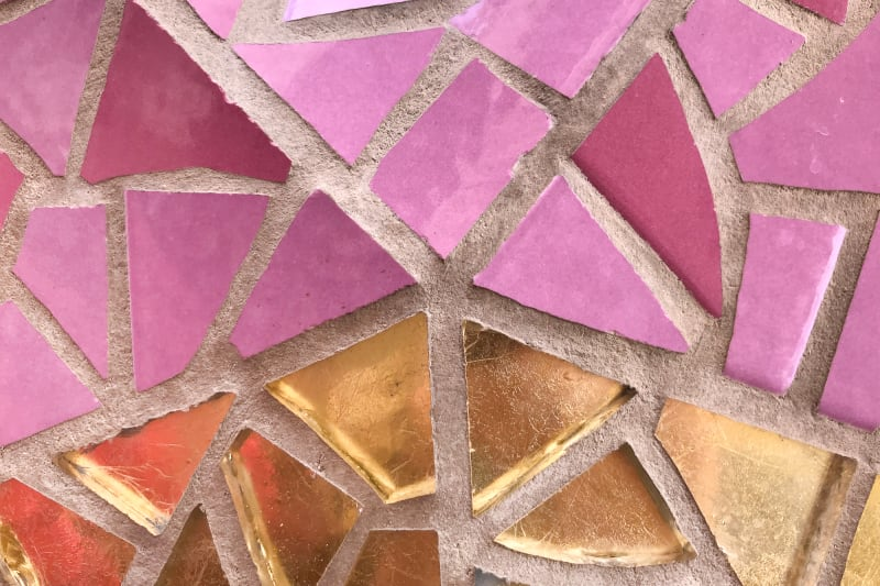 A close up of some tiled mosaic on the exterior of la Sagrada Família. The tiles are arranged in five segments like a pie chart. The top three segments are pink, and the bottom two are gold.