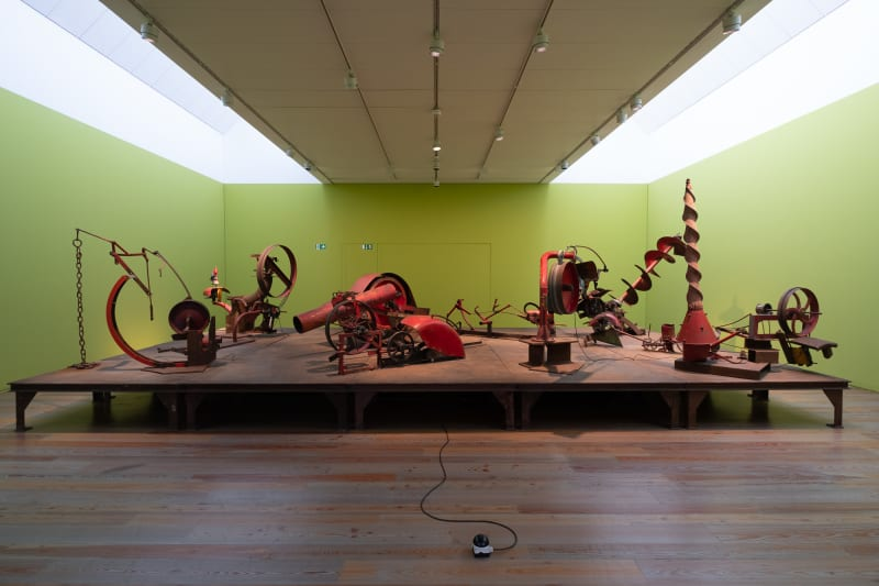 Wide photo of pale green room with several red mechanical sculptures in the middle.
