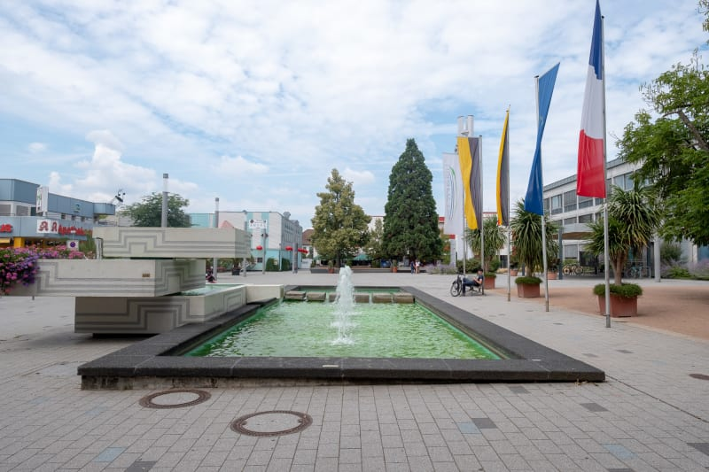 Facing straight on a rectangular fountain in an open air square. There's four flags on the right hand side.
