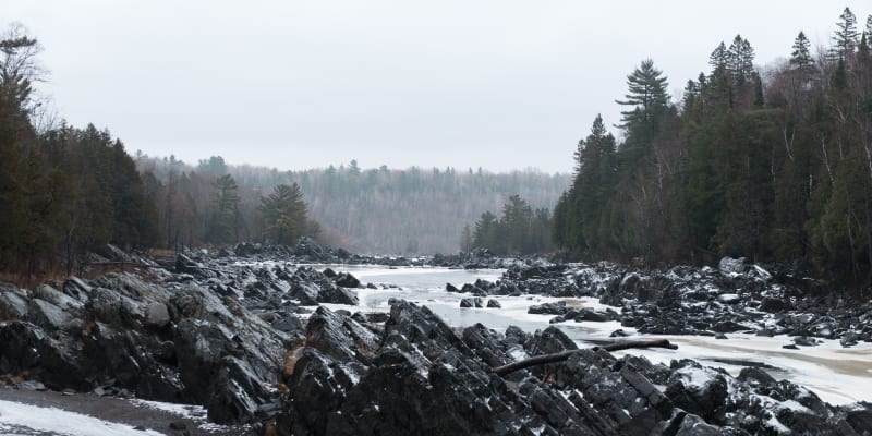 A long view across an icy river. There's dark rocky outcrops coming out of the river. The river is partially frozen with creamy patches of ice at the sides.