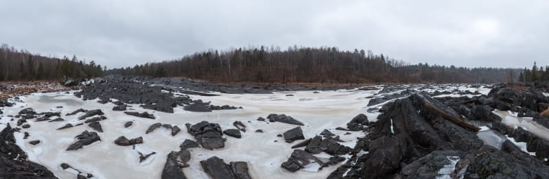 A panorama from the banks of an icy river. There's dark stones littering the riverbed and creamy ice in between.