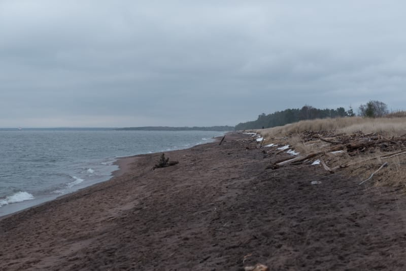 A photo from a grey beach looking along the shore.