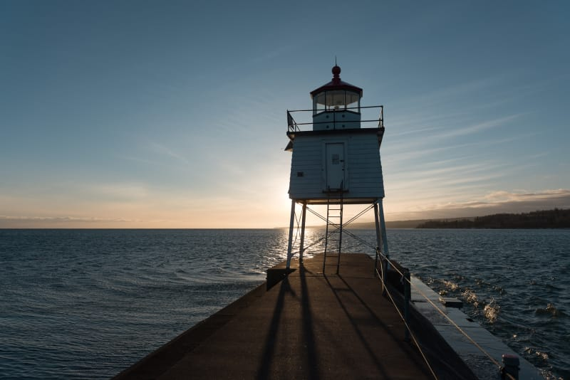 A small lighthouse at the end of a pier is silhouette in front of a setting sun.