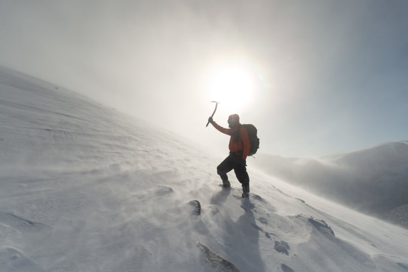Photo looking up a snowy hillside. Ed is in the foreground holding an axe above his head. The sun is nearly directly behind him.
