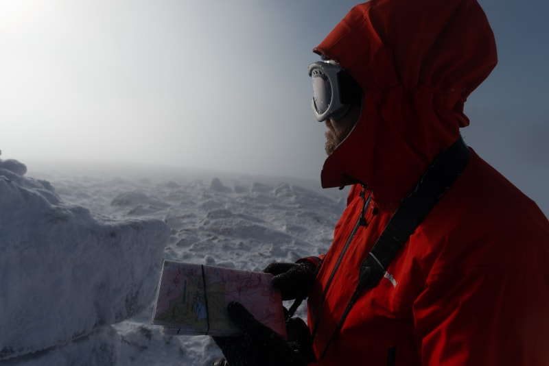 Ed looks out in to the distance, which is misty with low visibility. He's holding a map and compass, and wearing a bright orange jacket and ski goggles.