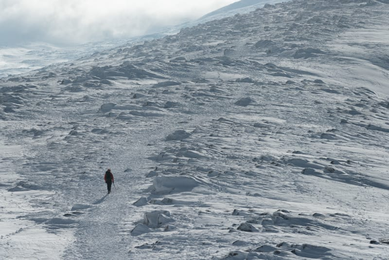 A telephoto photo of Ed walking up a wide snowy hill. He's a small dark figure in an otherwise very bleak landscape. There's an ice axe in his right hand.