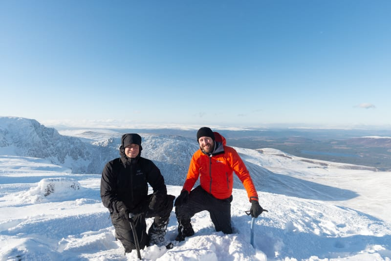 Ed and Chris kneel down with ice axes in hand at the top of Stob Coire an t-Sneachda