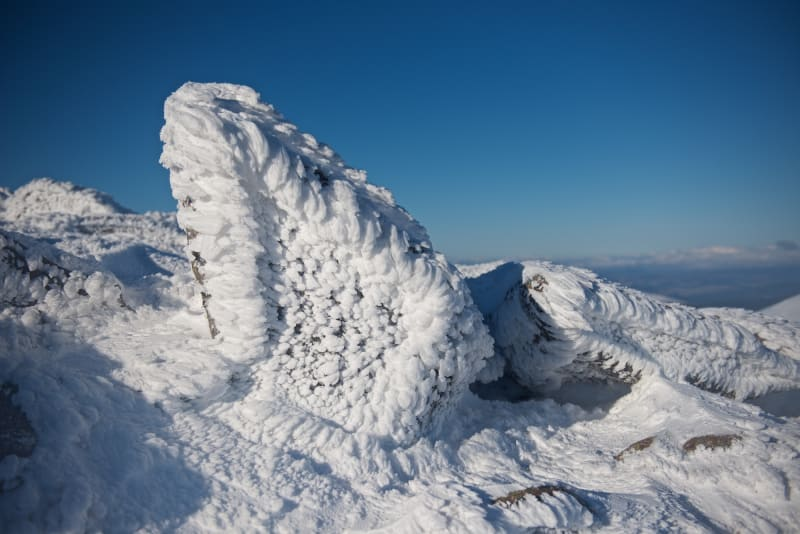Close photo of rime on rocks at the top of a snowy mountain.