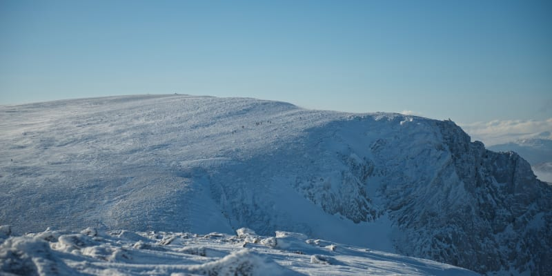 Looking across the edge of a snowy mountain. There's tiny specks from walkers on the hills