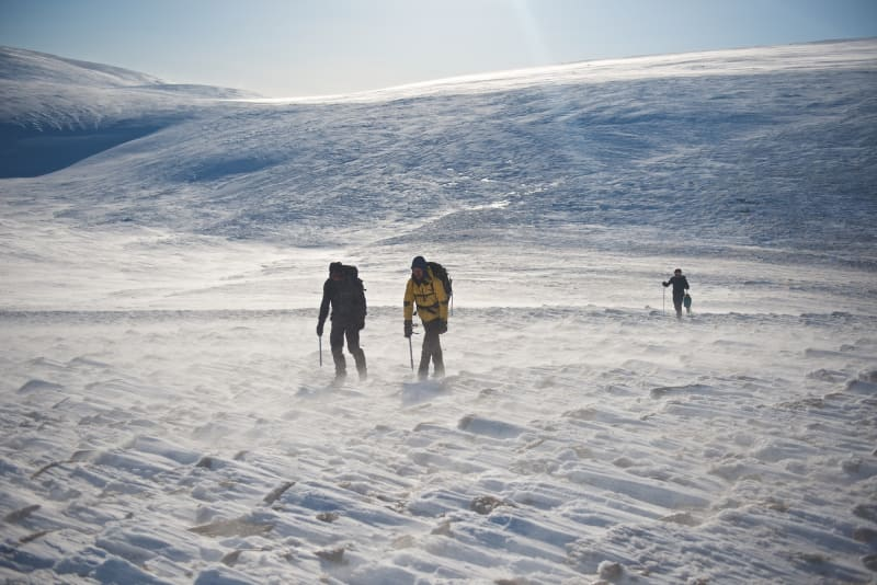 Two people walk across a snowy mountain, each holding an ice axe. There's two more behind them.