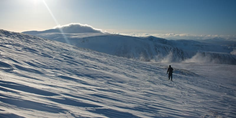 A man descending a snowy hillside in afternoon sun.