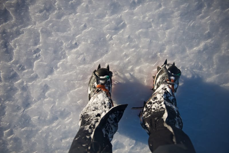 Looking down at a pair of boots with crampons on icy ground.