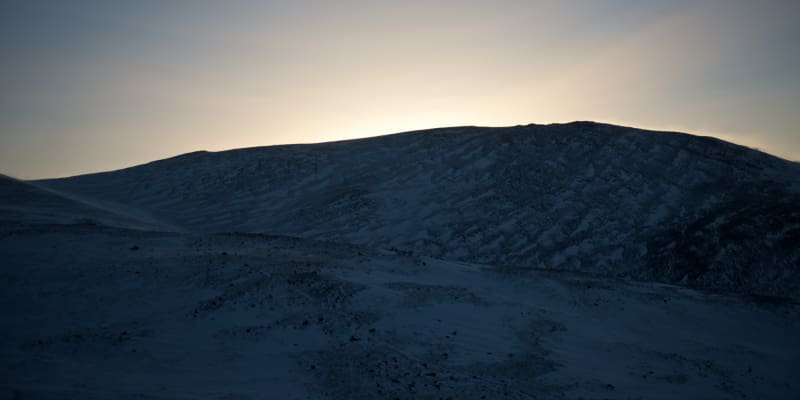 A panorama of a snowy hillside as the sun has set behind the hill.