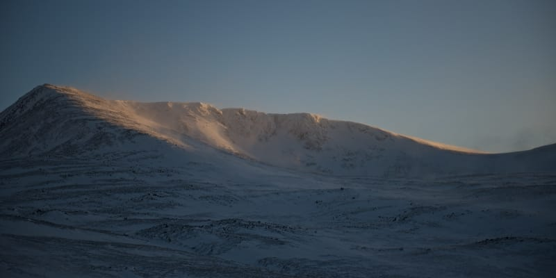 A wide panorama of a snowy mountainside as the sun sets.