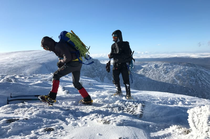 Two climbers in full winter gear at the top of a snowy mountain.