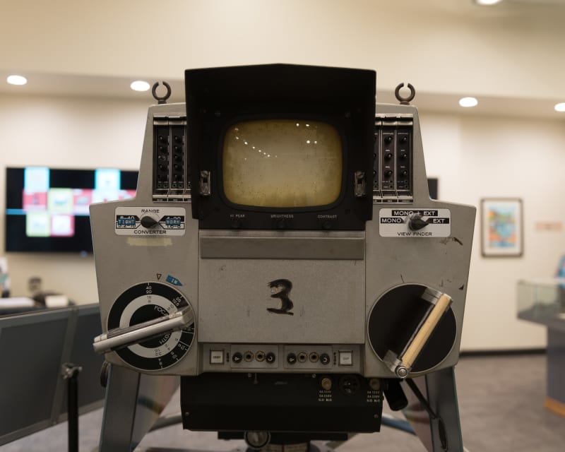 A photo of the rear of a vintage studio television camera as the operator would see it. There's two circular dials lower down, and a small CRT display in the center. The number '3' is written in marker in the middle.
