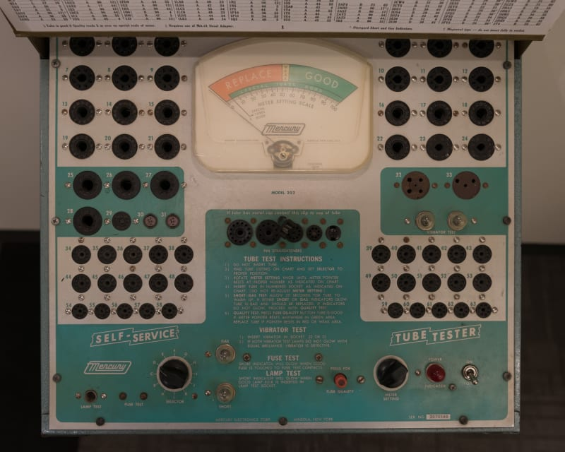 A photo of the front of a vintage 'tube tester'. The camera is looking directly down on a control panel. There's dials and inputs all over, with a large swinging gauge in the center.