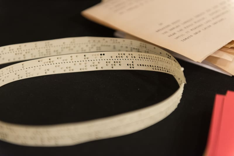A photo of telegraph signals encoded as morse code on a long ribbon of paper. The ribbon is about 1/2″ wide and and punched through with many dots.