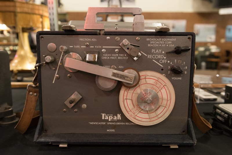 "A photo of the front of a vintage recording device. The device has a label on the front reading ""Tapak 'NewsCaster' spring-driven recorder"""