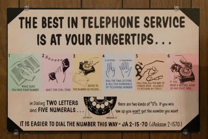 "Photo of a vintage poster describing with words and diagrams how to use a rotary telephone. The main reading reads ""The best in telephone service is at your fingertips..."" with a 6 step diagram for how to use a rotary phone."