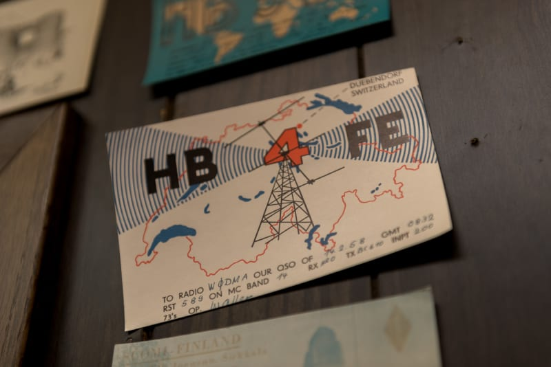 "A close macro photo of a vintage radio postcard. The postcard reads ""HB 4 FE"" and depicts a radio mast giving off signals inside an outline Switzerland."