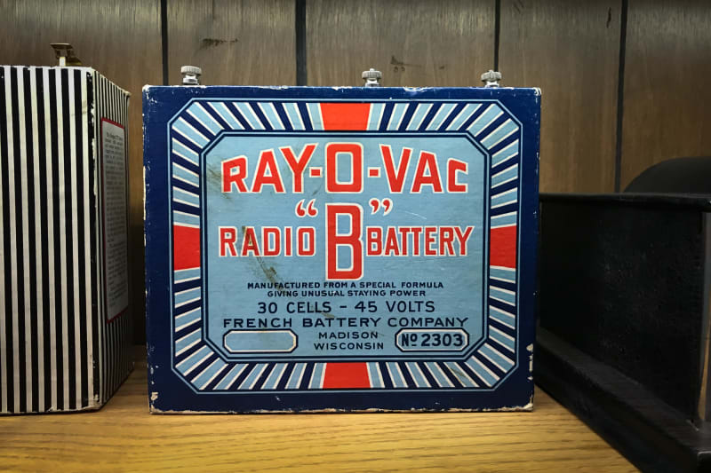 "Photo of the front of a vintage radio battery. The battery is brightly coloured with a graphic dark blue, light blue, white and red design. The front text reads ""Ray-o-vac radio 'B' battery"""