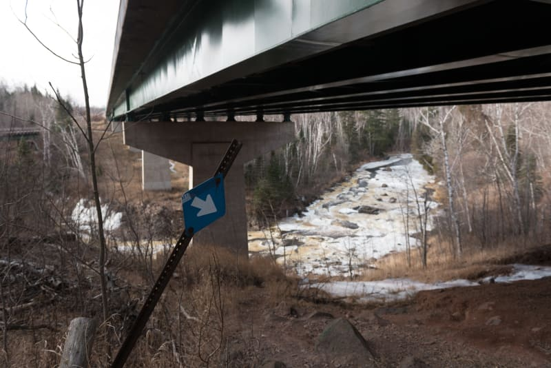 A photo taken from under highway 61 as it passes over the Baptism river. There's a blue arrow pointing to the right.