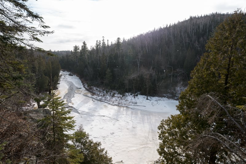 A photo taken from high up, overlooking a bend in Baptism river. The river is mostly covered in snow and ice. There's sparkles in the air from snow flying about.