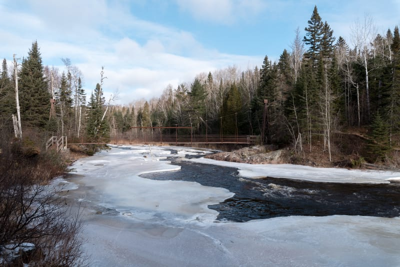 A photo down the banks of the Baptism river. The river is 70% covered in snow and ice, with a wire bridge in the background crossing the river.