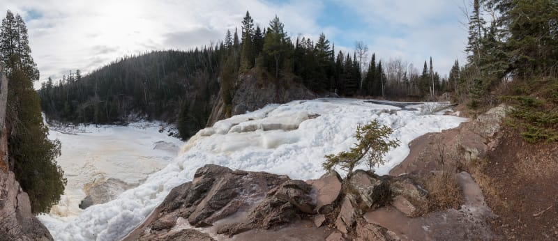 A panorama taken from the top of High Falls. The falls are partially frozen over with white and frothy ice.
