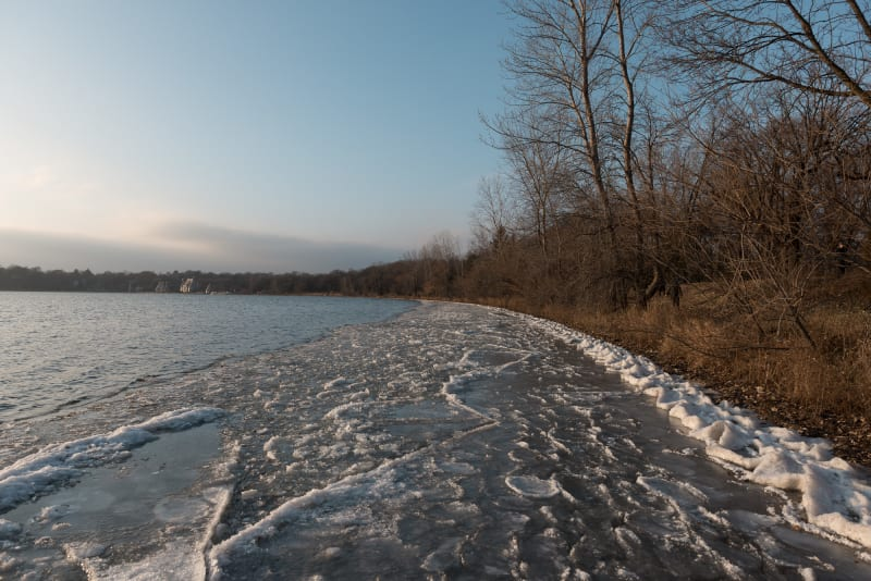 Looking along the shore of Lake Harriet. Close to the shore the edges of the lake have frozen in to intricate shapes. The banks are brown and autumnal.