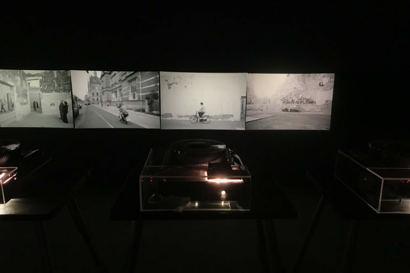 Five projectors in a dark room project black and white photos on to a wall.