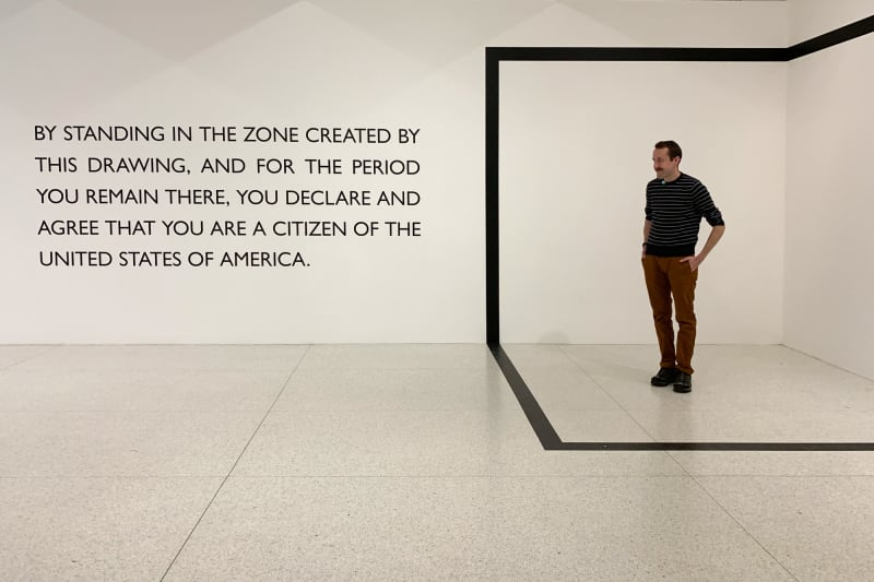"An area is marked off in the corner of a room in the shape of a cube. Ed Horsford stands in the area. To the left is a sign that reads ""By standing in the zone created by this drawing, and for the period you remain there, you declare and agree that you are a citizen of the United States of America.""."