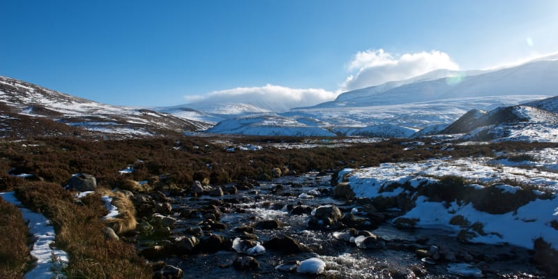 A small stream in a sunny valley landscape. There's patches of snow on the right bank.