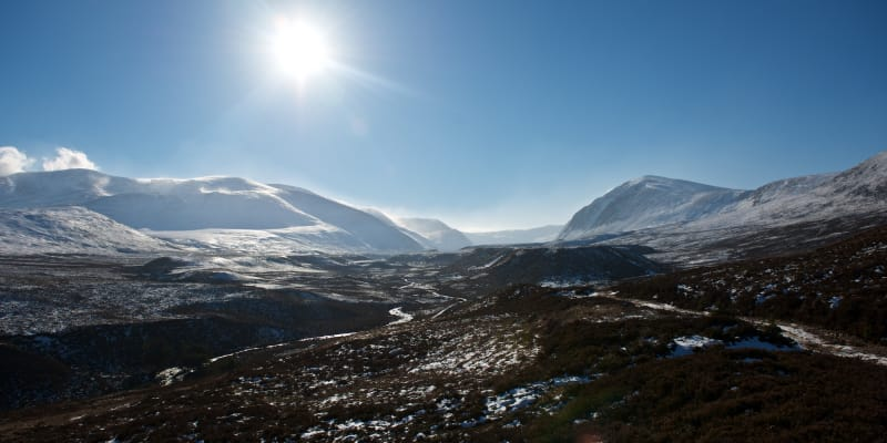A wide panorama of the Gleann Eanaich valley. There's snow on the upper parts of the mountains and in the valley it's mostly brown.