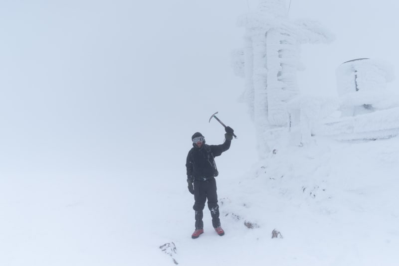 Ed Horsford standing next to the Cairngorm weather station, holding an ice axe over his head. The weather station is completely iced over and there's very little visibility.