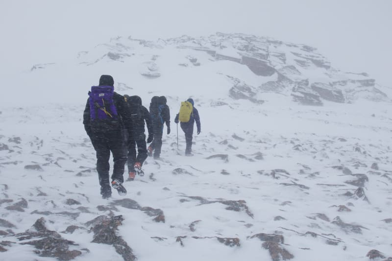 Four men dressed in winter gear walk in a line up a snowy mountain in poor visibility.