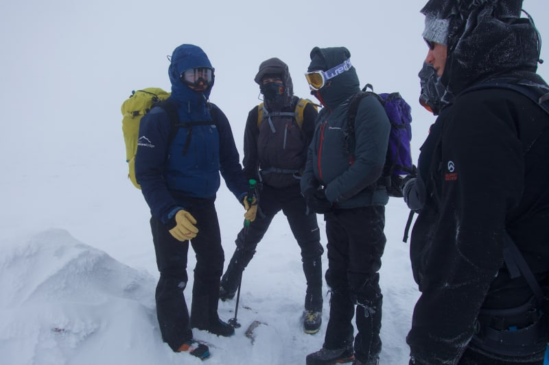 Four men wrapped up in winter clothing huddle on a snowy mountain.