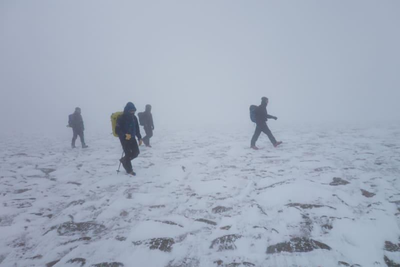 Four people walk on rocky and snowy ground in poor visibility.