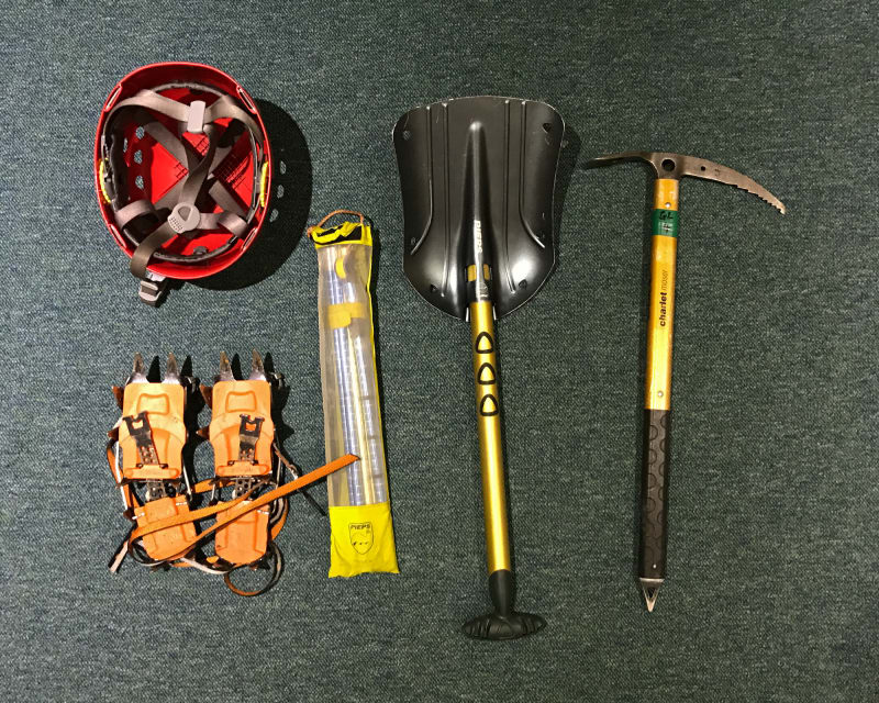 A selection of winter mountaineering tools on carpet. Pictured are a helmet, crampons, ice probe, shovel, and ice axe.