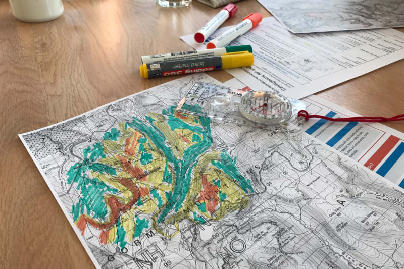 A black and white contour map of the Cairngorms on a table. Parts of it have been hand-coloured in yellow, orange, and green to indicate avalanche risk.