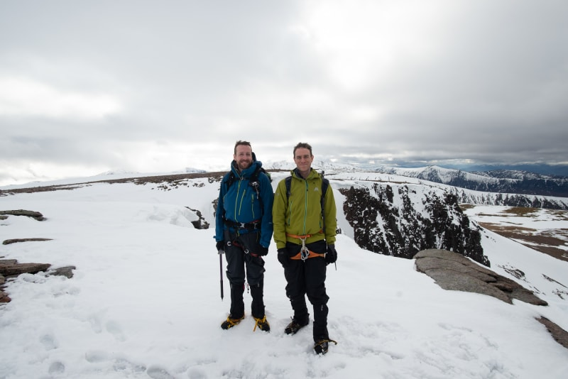 Chris and Ed stand at the top of Fiacaill ridge. The ground is mostly snowy with patches of brown.