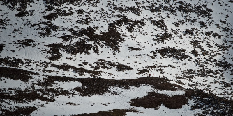A long photo of several hikers in the distance walking along a snowy path on a mountain side.