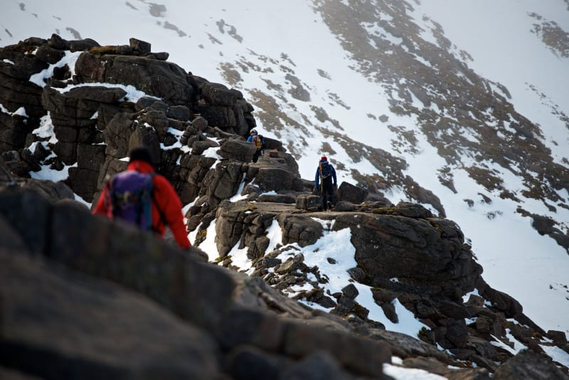 A photo taken facing along Fiacaill ridge. There's climbers walking along various sections of it, with one in the foreground.
