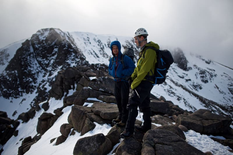 Chris and our instructor stand on a level section of Fiacaill ridge. There's low cloud on the mountain, but some sunlight just breaking through.