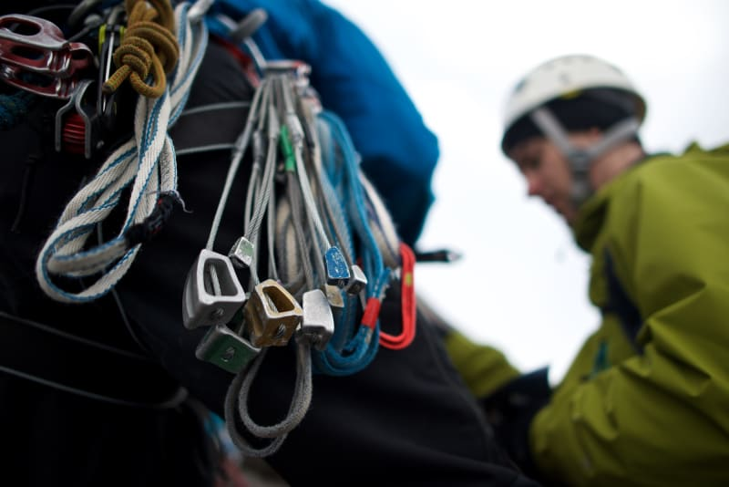 A macro photo of climbing gear on our instructor's harness. Chris is visible in the background.