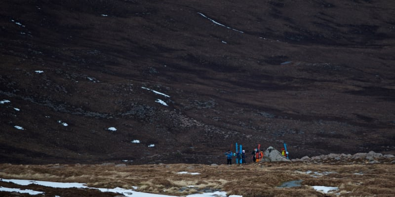 Long shot of several ski mountaineers in a valley. They have skied to the end of the snow, and are now packing up their gear.