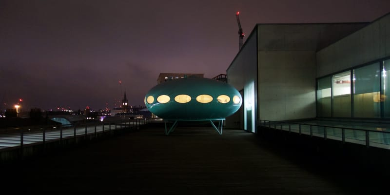 Facing straight on Futuro House. It's on the roof of a building on a cloudy night.